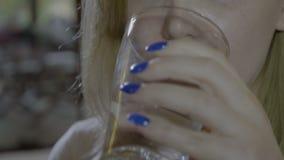 Κλείστε επάνω μιας νέας γυναίκας που καταπίνει ένα στρογγυλό μπλε χάπι και που πίνει ένα ποτήρι του νερού - φιλμ μικρού μήκους