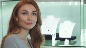 Κλείστε επάνω μιας προκλητικής όμορφης γυναίκας που χαμογελά στη κάμερα στο κατάστημα κοσμήματος απόθεμα βίντεο