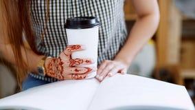 Κλείστε επάνω μιας συνεδρίασης γυναικών και γράψιμο στο περιοδικό της στην πολυάσχολη καφετερία απόθεμα βίντεο