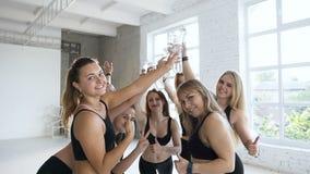 Κλείστε επάνω μπουκαλιών νερό ενός των ευτυχών νέων γυναικών κτύπου μετά από να εκπαιδεύσει στη γυμναστική Αθλητισμός και υγιής τ απόθεμα βίντεο