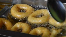 Κλείστε επάνω να τσιγαρίσει το δαχτυλίδι donuts στο πετρέλαιο απόθεμα βίντεο