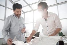 κλείστε επάνω οι αρχιτέκτονες συζητούν τα σκίτσα του νέου προγράμματος Στοκ Εικόνες
