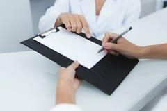 κλείστε επάνω Ο γραμματέας σε μια ιατρική κλινική βοηθά υπομονετικό τον πλήρη οι απαραίτητες μορφές πρίν αρχίζει τη θεραπεία στοκ εικόνες