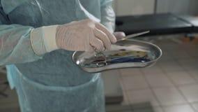 Κλείστε επάνω, ο χειρούργος παίρνει τα ιατρικά όργανα στο βραχίονά του από το χειρουργικό πίνακα Ο γιατρός παίρνει τα αποστειρωμέ φιλμ μικρού μήκους