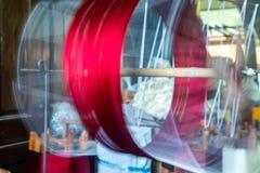 Κλείστε επάνω περιστρεφόμενο νήμα ροδών χαμηλής ταχύτητας το παλαιό με το κόκκινο Thre Στοκ Εικόνα