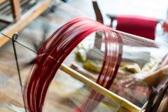 Κλείστε επάνω περιστρεφόμενο νήμα ροδών χαμηλής ταχύτητας το παλαιό με το κόκκινο Thre Στοκ Εικόνες