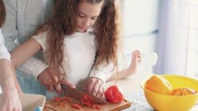Κλείστε επάνω, πιπέρι περικοπών πατέρων στον πίνακα κουζινών, η κόρη τον βοηθά, σε αργή κίνηση απόθεμα βίντεο