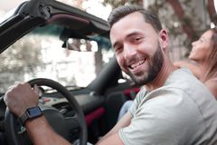 κλείστε επάνω πορτρέτο μιας συνεδρίασης ατόμων χαμόγελου πίσω από τη ρόδα ενός μετατρέψιμου αυτοκινήτου στοκ φωτογραφία