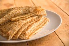 Κλείστε επάνω σε έναν σωρό διπλωμένος crepes οι γαλλικές τηγανίτες σε ένα πιάτο, ξύλινο υπόβαθρο Στοκ Εικόνες