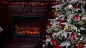 Κλείστε επάνω σε μια εστία δίπλα σε ένα χριστουγεννιάτικο δέντρο φιλμ μικρού μήκους