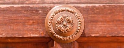 Κλείστε επάνω σε μια στρογγυλή λαβή πορτών με τα διακοσμητικά στοιχεία, πόρτα δ Στοκ Φωτογραφίες