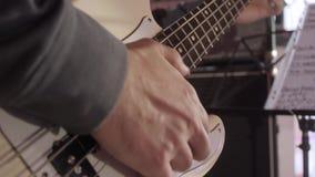 Κλείστε επάνω στα δάχτυλα του νεαρού άνδρα που παίζει τη βαθιά κιθάρα στο στάδιο απόθεμα βίντεο