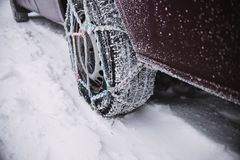 Κλείστε επάνω στη ρόδα αυτοκινήτων με τις αλυσίδες χιονιού Χειμερινό υπόβαθρο στοκ φωτογραφία με δικαίωμα ελεύθερης χρήσης