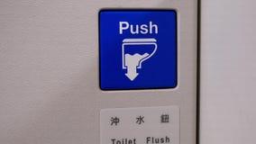 Κλείστε επάνω στο επίπεδα κουμπί τουαλετών και το σημάδι ώθησης απόθεμα βίντεο