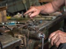 Κλείστε επάνω στο πιάσιμο σιδήρου που τοποθετείται στο εργαστήριο πάγκων εργασίας στο σπίτι Σύνολο Worktop του διαφορετικού χεριο Στοκ φωτογραφία με δικαίωμα ελεύθερης χρήσης
