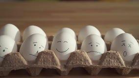Κλείστε επάνω τα αυγά κοτόπουλου με τα χρωματισμένα πρόσωπα σε ένα κουτί από χαρτόνι απόθεμα βίντεο
