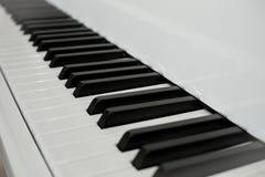 Κλείστε επάνω τα γραπτά κλειδιά κλειδιών πιάνων προοπτική από το πληκτρολόγιο πιάνων Στοκ Φωτογραφίες