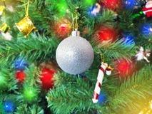 Κλείστε επάνω τα εξαρτήματα Χριστουγέννων που κρεμούν διακοσμημένος με το χριστουγεννιάτικο δέντρο φω'των Διακοσμήσεις Χριστουγέν στοκ φωτογραφίες
