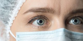 Κλείστε επάνω τα ευρέως ανοιγμένα μάτια του γιατρού Θηλυκός γιατρός στο protecti στοκ εικόνες
