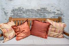 Κλείστε επάνω τα ζωηρόχρωμα μαξιλάρια στον ξύλινο καναπέ στοκ εικόνες