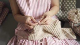 Κλείστε επάνω τα θηλυκά πλέκοντας χέρια Συνεδρίαση μαλλιού πλεξίματος χόμπι γυναικών στον καναπέ φιλμ μικρού μήκους