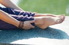 Κλείστε επάνω τα θηλυκά χέρια κρατώντας η συνεδρίαση ότι ποδιών θέτει στοκ φωτογραφία