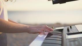 Κλείστε επάνω τα θηλυκά χέρια παίζοντας το πιάνο με το δάχτυλο στη χορδή και το ελαφρύ ηλιοβασίλεμα στο αριστερό, και το διάστημα φιλμ μικρού μήκους