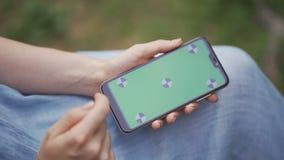 Κλείστε επάνω τα θηλυκά χέρια που κρατούν το smartphone και που κοιτάζουν βιαστικά τον ιστοχώρο φιλμ μικρού μήκους