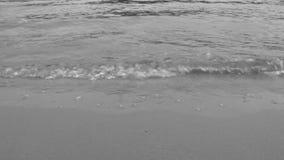 Κλείστε επάνω τα κύματα των ρόλων ποταμών επάνω στην αμμώδη ακτή φιλμ μικρού μήκους