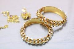 Κλείστε επάνω τα λαμπρά χρυσά κοσμήματα στο άσπρο ύφασμα Στοκ εικόνες με δικαίωμα ελεύθερης χρήσης
