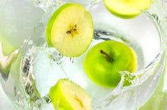 Κλείστε επάνω τα πράσινα μήλα που εμπίπτουν στο νερό με τον παφλασμό Στοκ Εικόνα