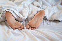 Κλείστε επάνω τα πόδια του ύπνου μικρών παιδιών στο κρεβάτι στοκ φωτογραφία