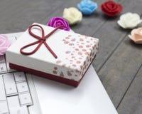 Κλείστε επάνω τα τριαντάφυλλα, το άσπρο lap-top και το κόκκινο κιβώτιο δώρων στο υπόβαθρο στοκ φωτογραφία