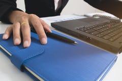 Κλείστε επάνω τα χέρια ανθρώπων που τοποθετούνται στο σημειωματάριο στοκ εικόνες