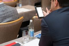 Κλείστε επάνω τα χέρια ατόμων που κρατούν και που χρησιμοποιούν το κινητό τηλέφωνο στη συνεδρίαση στοκ φωτογραφίες