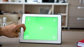 Κλείστε επάνω τα χέρια ατόμων σχετικά με ένα ψηφιακό PC talbet με την πράσινη χλεύη χρώματος οθόνης επάνω απόθεμα βίντεο