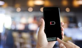 Κλείστε επάνω τα χέρια ατόμων χρησιμοποιώντας την έξυπνη τηλεφωνική μπαταρία χαμηλή φορτισμένη μπαταρία Στοκ εικόνα με δικαίωμα ελεύθερης χρήσης