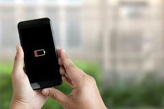 Κλείστε επάνω τα χέρια ατόμων χρησιμοποιώντας την έξυπνη τηλεφωνική μπαταρία χαμηλή φορτισμένη μπαταρία Στοκ εικόνες με δικαίωμα ελεύθερης χρήσης