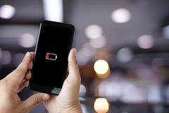 Κλείστε επάνω τα χέρια ατόμων χρησιμοποιώντας την έξυπνη τηλεφωνική μπαταρία χαμηλή φορτισμένη μπαταρία Στοκ Εικόνες