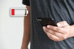 Κλείστε επάνω τα χέρια ατόμων χρησιμοποιώντας την έξυπνη τηλεφωνική μπαταρία χαμηλή φορτισμένη μπαταρία Στοκ Φωτογραφίες