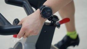 Κλείστε επάνω τα χέρια γυναικών με το βραχιόλι ικανότητας ή το έξυπνο ρολόι handlebars του στατικού εσωτερικού ποδηλάτου κατά τη  φιλμ μικρού μήκους