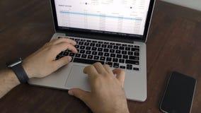 Κλείστε επάνω τα χέρια ενός ατόμου που δακτυλογραφεί στο πληκτρολόγιο στο νόμισμα cripto γραφείων και διαγραμμάτων ρολογιών απόθεμα βίντεο