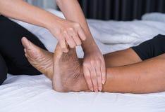 Κλείστε επάνω τα χέρια που κάνουν το μασάζ στα πόδια πόνου ηλικιωμένων γυναικών στο κρεβάτι Στοκ εικόνες με δικαίωμα ελεύθερης χρήσης