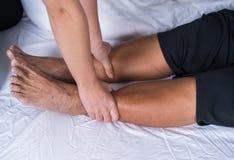 Κλείστε επάνω τα χέρια που κάνουν το μασάζ στα πόδια πόνου ηλικιωμένων γυναικών στο κρεβάτι Στοκ Φωτογραφία