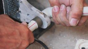 Κλείστε επάνω τα χέρια που συγκολλούν τους μέταλλο-πλαστικούς σωλήνες με το συγκολλώντας σίδηρο Υδραυλικός που συγκολλά τους πλασ απόθεμα βίντεο