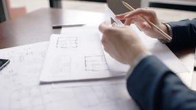 Κλείστε επάνω τα χέρια του αρσενικού αρχιτέκτονα που καθιστά hause το σχεδιάγραμμα στην αρχή απόθεμα βίντεο