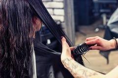 Κλείστε επάνω τα χέρια του θηλυκού επαγγελματικού κομμωτή που κτενίζει το υγρό εκτάριο Στοκ εικόνες με δικαίωμα ελεύθερης χρήσης