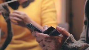 Κλείστε επάνω τα χέρια του συνταξιούχου που κάνει την πληρωμή με πιστωτική κάρτα για Διαδίκτυο που ψωνίζει στο smartphone απόθεμα βίντεο