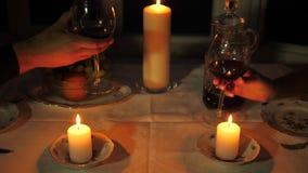 Κλείστε επάνω τα χέρια των ποτηριών κουδουνίσματος ανδρών και γυναικών του κρασιού για ένα ρομαντικό γεύμα φιλμ μικρού μήκους