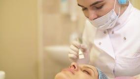 Κλείστε επάνω τα χέρια beautician εφαρμόζει την κρέμα στο υπομονετικό πρόσωπο μετά από τη θεραπεία και το μασάζ Έννοια cosmetolog φιλμ μικρού μήκους